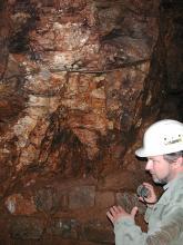 Das Bild zeigt die dunkelrotbraune Stollenwand eines Bergwerks. Ein Mitarbeiter des LGRB ist am rechten Bildrand zu sehen.