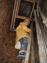 Das Bild zeigt die dunkelbraunen Wände eines Bergwerkschachtes mit angelegter Leiter und oben eingelassenem Gitter. Eine Besucherin blickt von der Leiter nach unten.