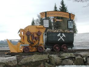 Blick auf eine schwarzgraue Lore, mit Erz gefüllt, sowie ein gelbes Räumfahrzeug. Beides weist auf ein Museumsbergwerk hin.