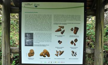 Blick auf eine überdachte Schautafel im Naturpark Schönbuch mit Bildern fossiler Zähne und Fischschuppen..