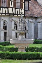 Das Bild zeigt einen aus weißlich-grauem Gestein gefertigten, mehrstufigen Brunnen. Im Hintergrund eine Kirchenfassade mit gotischen Fensteröffnungen; darüber ein Fachwerkanbau und Fenster mit Läden.