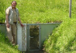 Am Fuße eines Wiesenhanges wurde ein Bodenprofil freigelegt und danach mit einer metallenen Schutzwand gesichert. Eine Glastür erlaubt die Besichtigung des Profils. Ein ehemaliger Mitarbeiter der Bodenkunde zeigt auf die Beschreibung des Profils.