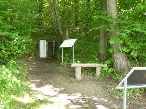 Auf einer kleinen Waldlichtung sind unter anderem zwei Schautafeln aus Metall sowie ein in eine Böschung eingelassenes metallenes Gitter mit Tür zu sehen. Die Tür ist geöffnet und zeigt den inneren Aufbau der Böschung.