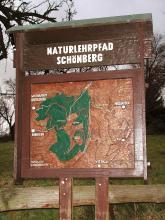 Blick auf eine hölzerne, überdachte Schautafel, die auf den Naturlehrpfad am Schönberg hinweist.