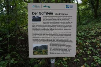 """Gezeigt wird hier eine Schautafel des Naturparks Neckartal-Odenwald mit dem Thema """"Der Gaffstein"""". Die Tafel steht vor Bäumen und Sträuchern."""