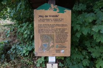 """Aufgestellt ist hier eine hölzerne Hinweistafel als Station des mineralogischen Lehrpfades """"Weg der Kristalle"""" am ehemaligen Vulkan Katzenbuckel im Odenwald."""