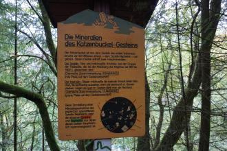 """Blick auf eine hölzerne Schautafel mit dem Thema: """"Die Mineralien des Katzenbuckel-Gesteins"""". Die Tafel ist mitten im Wald an einem Baum befestigt."""
