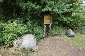 Zwischen zwei größeren Steinbrocken, auf einem ausgetretenen Pfad, steht eine Schautafel aus Holz. Die Tafel wird von einem Nadelbaum überragt. Daneben wächst Buschwerk.