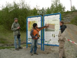 Hier werden zwei Schautafeln zu einem Geologischen Lehrpfad gezeigt. Die Tafeln stehen auf kiesigem Untergrund und vor teilweise abgesperrtem Gelände. Drei Herren mit Mützen und Jacken betrachten die Tafeln.