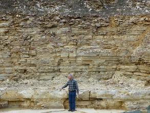 Blick auf eine Steinbruchwand mit rötlichem bis grauem, waagrecht gebanktem Gestein unterschiedlicher Höhe. Ein Mann, der vor der Steinbruchwand steht, wendet sich an mögliche, nicht sichtbare Besucher.