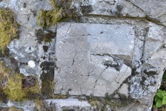 Blick auf teils mit Moos bewachsenes, teils freiliegendes hellgraues Gestein. Auffallend ist eine quadratische geschliffene Platte, die vom restlichen Gestein durch einen gemeißelten Rand getrennt ist. Rechts sind Stücke aus der Platte herausgebrochen.