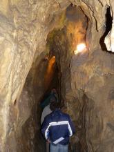 Blick in einen hohen, schmalen und von künstlichem Licht erhellten Höhlengang, in dem gerade eine kleine Gruppe von Besuchern unterwegs ist.