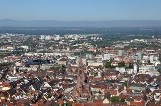 Von sehr hohem Standort blickt man über die ausgedehnten Häuserzeilen einer größeren Stadt. In der unteren Bildmitte erhebt sich ein gotisches Münster. Im dunstigen Hintergrund ist eine Bergkette erkennbar.