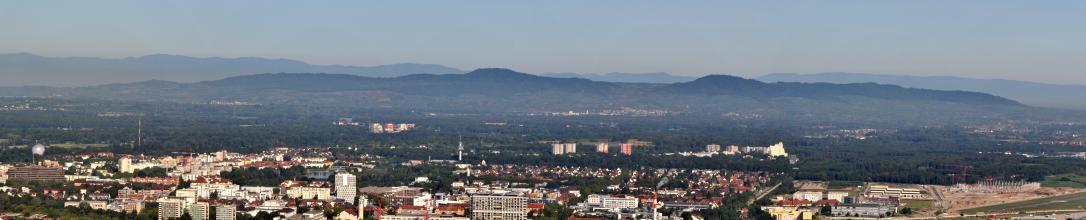 Panoramabild einer größeren Stadt mit Altstadt- und Hochhäusern. Rechts unten ist eine größere Baustelle zu erkennen. Den Hintergrund bilden bewaldete Hügel- und Bergketten.