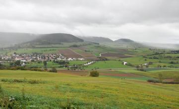 Das Foto zeigt eine meist grüne, hügelige Landschaft. An den Hängen von im Hintergrund sich erhebenden Bergen sind auch Äcker erkennbar. Die Bergkuppen sind bewaldet. Im Mittelgrund schlängelt sich ein Fluss. Links hinten liegt eine Siedlung.