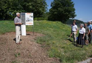 Links im Bild wird hier eine hinter Glas ausgestellte Bodenstele mit angebauter Schautafel gezeigt. Ein Mann erzählt einer Gruppe von Zuhörern wohl gerade etwas über diese Stele.