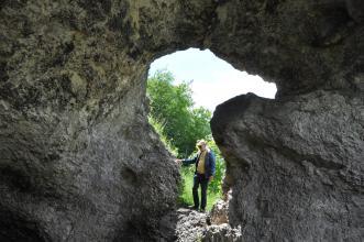 Blick durch eine Felsöffnung ins Freie. Die Öffnung hat die Form eines Vogelkopfes, der nach rechts schaut. Am Fuß der Öffnung steht ein Mann, der mit seiner rechten Hand den Felsen berührt.