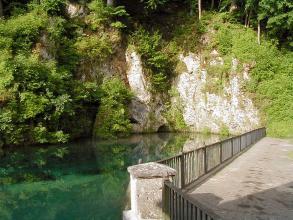Das Bild zeigt einen türkisblauen See, an den sich rechts eine steinerne Plattform anschließt. Hinter dem See ragen teils helle, stark bewachsene Felsen mit kleinen Nischen und Höhlen empor.