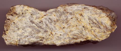 Großaufnahme eines länglichen Steins mit teils abgerundeten Kanten. Die glattgeschliffene Schauseite ist weißlich grau mit gelben Sprenkeln.