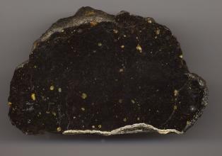 Nahaufnahme eines Gesteinsbrockens mit rundlicher, unregelmäßiger Form und glatter Oberfläche. Das Gestein ist schwarz mit gelblichen Einschlüssen. Am unteren Rand befindet sich ein weißlicher Streifen.