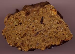 Nahaufnahme eines Gesteinsbrockens mit geschliffener Oberfläche und abgerundeten Kanten. Das Gestein ist von rostbrauner Farbe mit dunkleren Einschlüssen.