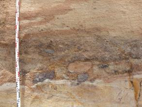 Nahaufnahme von hellbraunem bis rötlichem Sand. In der unteren Bildhälfte ovale violettfarbene Einschlüsse. Ganz rechts unten ist ein orangefarbener Keil erkennbar. Links ist ein Maßband angelehnt.