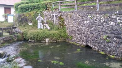Blick auf eine mit einer Brüstung versehene, halbhohe Steinmauer (rechts im Bild). Am unteren Rand der Mauer, aus einer kleinen Öffnung, fließt Wasser. Dieses Wasser, das einen Teich bildet und von Algen durchsetzt ist, fließt links in einen flachen Fall.