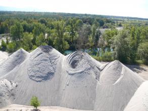 Das Bild zeigt mehrere nebeneinander aufgeschichtete, hellgraue Kieshaufen in Kegelstumpf- oder Kegelform. Im Hintergrund ausgedehnte Waldflächen.
