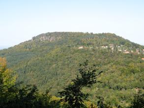 Blick aus großer Entfernung auf einen hohen, bewaldeten Bergrücken. Links oben ragen rötliche Felszinnen aus dem Bergwald, rechts tauchen einzelne Häuser zwischen den Bäumen auf.