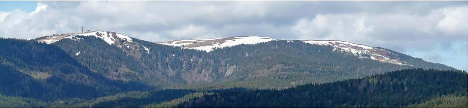 Panoramabild von bewaldeten, nebeneinander liegenden Bergen mit von Schnee bedeckten Gipfeln. Auf dem linken, höchsten Gipfel ist ein Aussichtsturm erkennbar.