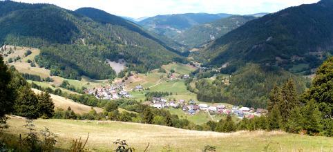 Von erhöhtem Standpunkt schaut man in einen von bewaldeten Bergen eingefassten Talkessel mit bleichen Wiesen und kleineren, verteilten Siedlungen.