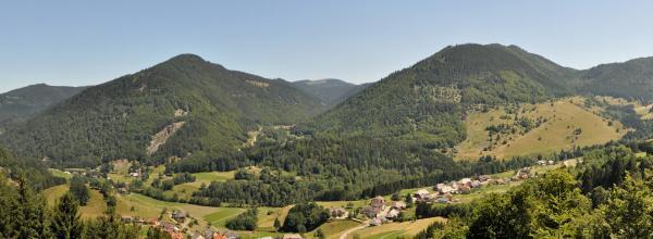 Panoramabild zweier hoher, nebeneinander liegender bewaldeter Berge. Rechts unten sowie links vorn verteilen sich Häuser mit Walmdächern.