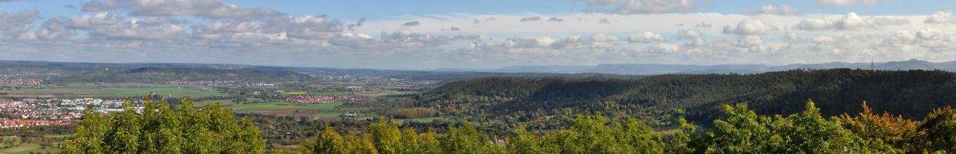 Panoramabild mit links dicht besiedelten Ebenen und rechts stark bewaldeten Hängen. Im Hintergrund erheben sich weitere bewaldete Höhenzüge.