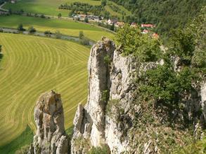 Aus großer Höhe blickt man auf teils kahle, teils mit Bäumen bewachsene weißlich bis bräunlich graue Felstürme. Darunter breiten sich befahrene Grünflächen, ein schmaler Fluss sowie eine kleine Siedlung aus.
