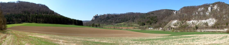 Das Panoramabild zeigt weite Acker- und Grünlandflächen, an die sich nach links und rechts steile, bewaldete Höhenzüge anschließen. Rechts durchbrechen weißliche Felsen und Schutthänge den Wald.