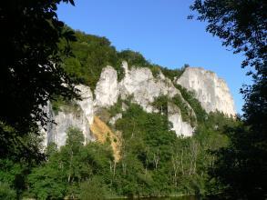 Oberhalb eines gerade noch erkennbaren Flusses und inmitten dichter Bewaldung erheben sich mehrere schroffe, steile, weißlich graue Felstürme. In der Bildmitte links ist zudem eine gelblich gefärbte Schutthalde zu sehen.
