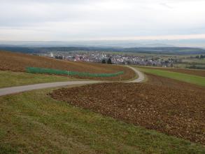 Das Bild zeigt - von einem kurvigen Weg getrennt - teilweise gepflügte und sehr kiesreiche Ackerflächen, die nach rechts absinken. Im Hintergrund sind eine größere Siedlung, mehrere bewaldete Höhenzüge sowie eine Bergkette erkennbar.