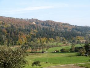 Blick über ein flaches Tal mit Wiesen, Äckern und Bäumen. Im Hintergrund erhebt sich, nach links ansteigend, ein bewaldeter Berg.