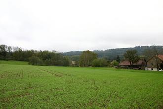 Blick auf bepflanzte Äcker, ein Gehöft rechts und Baumstreifen. Im Hintergrund bewaldete Höhenrücken.