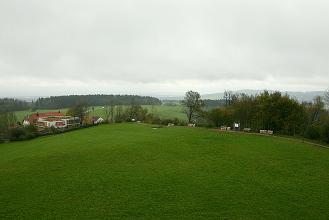 Blick von einer grünen Erhebung auf einzelne Häuser, Wiesen und Waldstreifen.