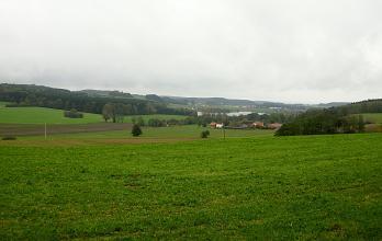 Blick auf eine leicht hügelige grüne Landschaft mit wenigen Äckern und bewaldeten Höhen. Im Bildhintergrund ist zudem ein See erkennbar.