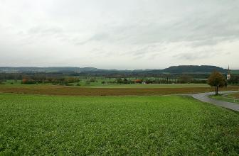Blick über eine weite, von Äckern und Waldstreifen durchzogene Wiesenlandschaft. Im Hintergrund bewaldete Höhenrücken.