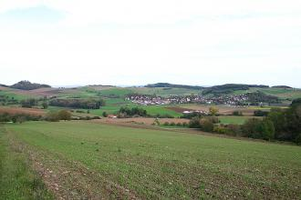 Hinter einem Acker ist eine hügelige Landschaft mit vereinzelten Siedlungen und Waldstücken zu sehen.