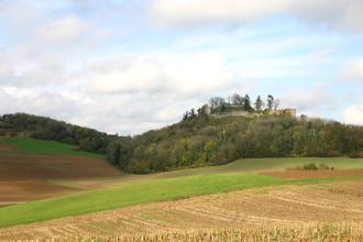 Hinter wellenförmig geformten, hügeligen Äckern und Wiesen im Vordergrund erhebt sich ein bewaldeter, flacher Berg mit einer Burgruine.