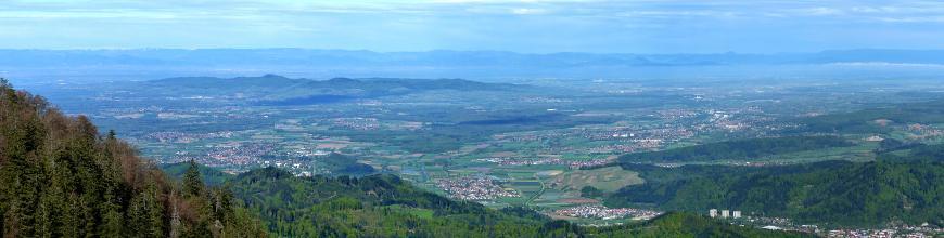 Blick von erhöhtem Standort über eine weite, zersiedelte Landschaft mit Feldern und Waldflächen. Im Mittelgrund liegt eine Gruppe niedriger bewaldeter Berge, am dunstigen Horizont sind höhere Berge zu erkennen.