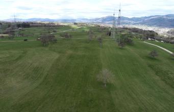 Blick von oben auf eine hügelige, von Fahrwegen und Strommasten durchzogene, höhergelegene Wiesenlandschaft. Im Hintergrund rechts ist hinter Wald eine Siedlung erkennbar. Noch weiter zurück verläuft eine bewaldete Bergkette.