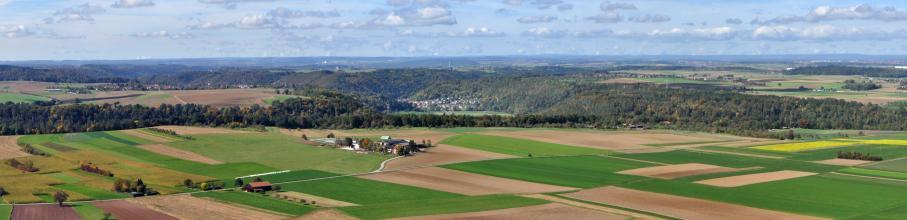 Von erhöhtem Standpunkt aus geht der Blick auf schachbrettartig angelegte Acker- und Grünlandflächen, ehe sich weiter hinten bewaldete Hänge mit bwirtschafteten Ebenen abwechseln. Noch weiter entfernt sind verschiedene Höhenzüge erkennbar.