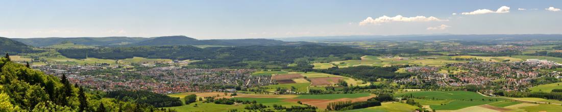 Panoramabild eines wellig-hügeligen Mosaiks aus Grünland- und Ackerflächen mit größeren Siedlungen links und rechts sowie im Hintergrund. Auch große Waldflächen und bewaldete Höhenrücken durchziehen die Landschaft.