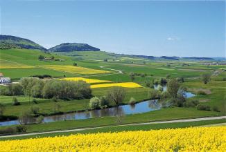 Der Blick geht über ein gelbes Rapsfeld auf eine weite grüne Landschaft, die nach links hin zu zwei bewaldeten Bergkuppen ansteigt. Im Vordergrund durchschneidet ein Fluss s-förmig die Aue, gesäumt von einzelnen Bäumen.