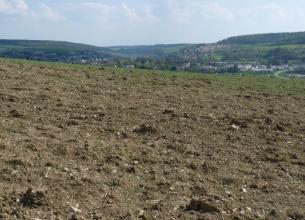 Das Bild zeigt einen lockeren, leicht nach rechts geneigten, steinigen braunen Acker. Im Hintergrund sind ausgedehnte Siedlungen sowie bewaldete Hänge erkennbar.
